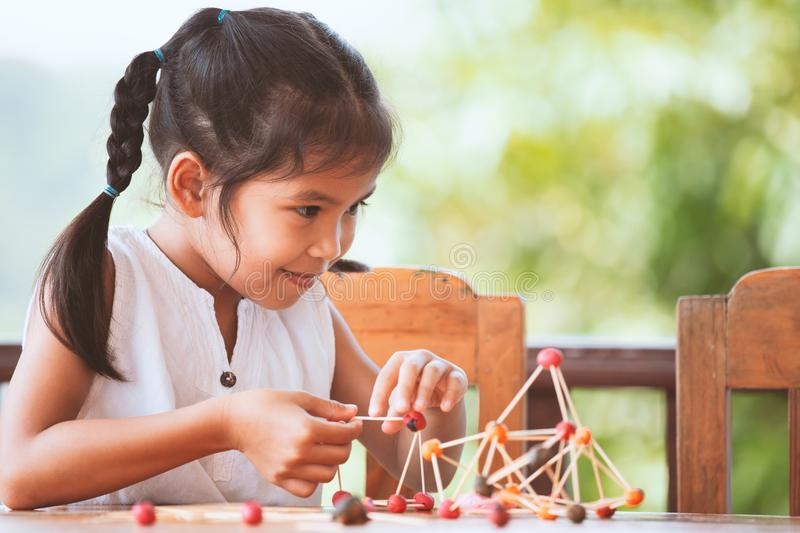 Cute asian child girl playing and creating with play dough. And toothpick. Child concentrated with play dough building a molecule model stock photo
