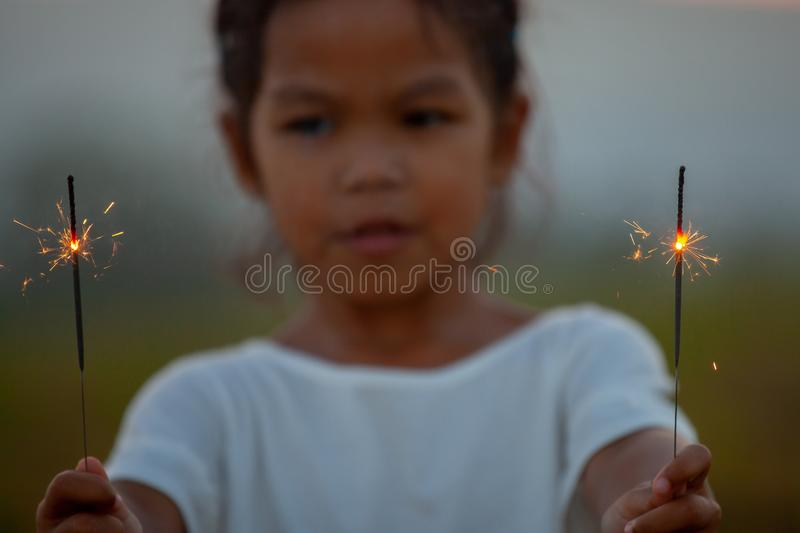 Cute asian child girl are playing with fire sparklers. On the festival in the rice field at sunset royalty free stock image