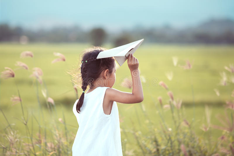 Cute asian child girl playing toy paper airplane in the field. In vintage color tone stock images