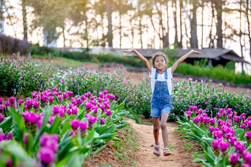 Cute asian child girl raise their arms and run in the flower garden. With freshness and happiness royalty free stock images