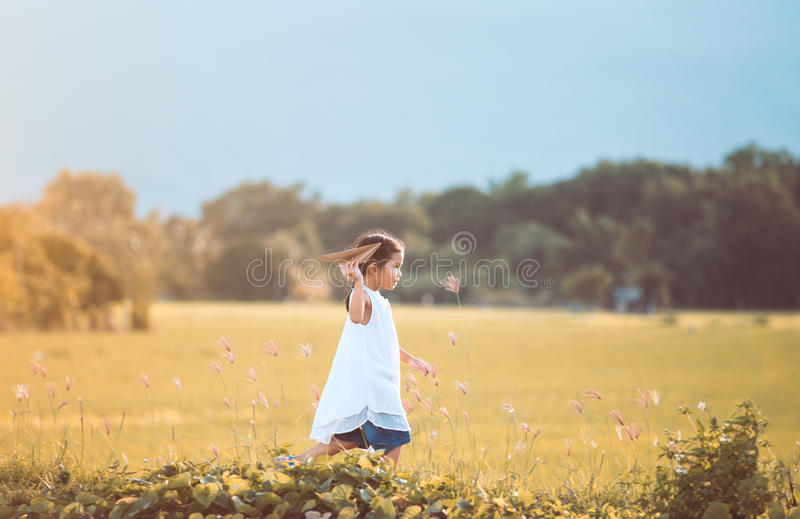 Cute asian child girl running and playing toy paper airplane. In the field in vintage color tone royalty free stock images
