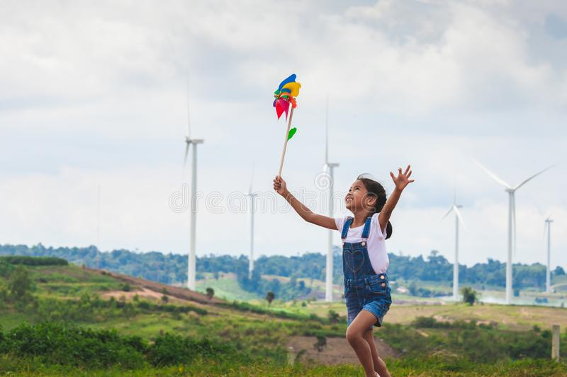 Asian child girl is running and playing with wind turbine toy  with fun in the wind turbine field stock images