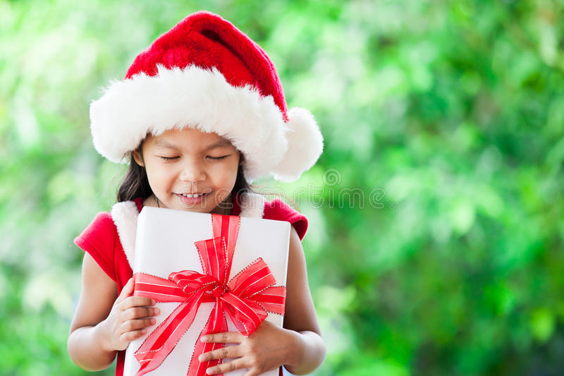 Cute asian child girl in santa red hat holding Christmas gift. In hand on green nature background. Christmas concept stock photos