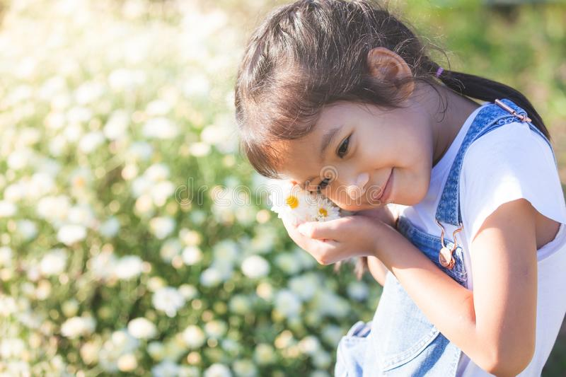 Cute asian child girl smiling and holding small flower in hand stock photo