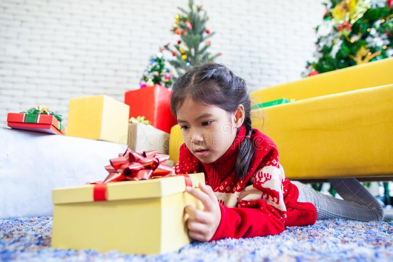 Asian child girl surprise with gift and holding beautiful gift box in hand on Christmas celebration. Cute asian child girl surprise with gift and holding stock photography