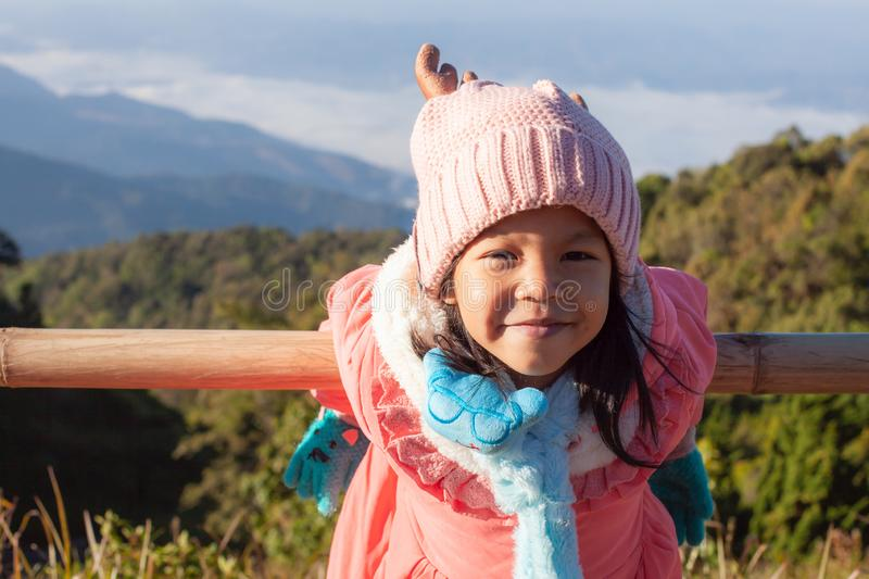 Cute asian child girl wearing sweater and warm hat smiling and happy when travel with family at beautiful nature stock photo