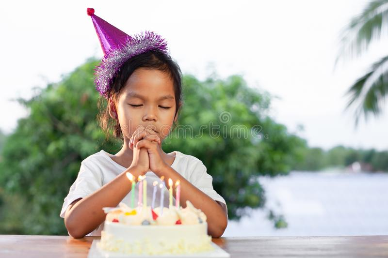 Asian child girls make folded hand to wish the good things for her birthday in birthday party. Cute asian child girls make folded hand to wish the good things stock images