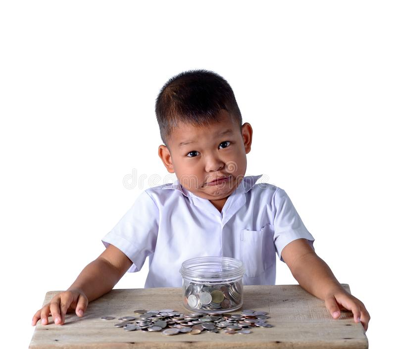 Cute asian country boy have fun with coins in Glass bowl isolated on white background. Cute asian country boy in school uniform have fun make funny faces with royalty free stock image