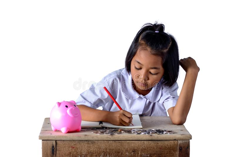 Cute asian country girl Make a note of income receipts and coins with piggy bank isolated on white background. Cute asian country girl in school uniform Make a royalty free stock photo