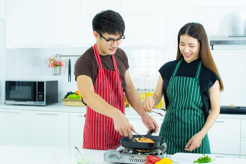 A couple is cooking in the kitchen stock photos