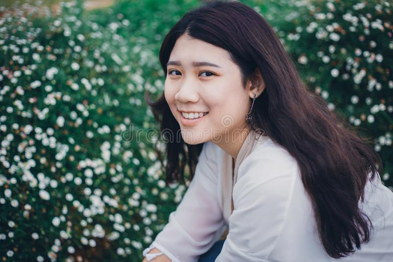 Cute Asian Fat Teen Girl Young Smiling with Healthy Tteeth in the garden flower field vintage color tone stock photo