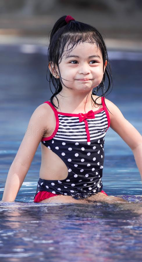 Cute asian female toddler child while playing on water in a swimming pool stock images