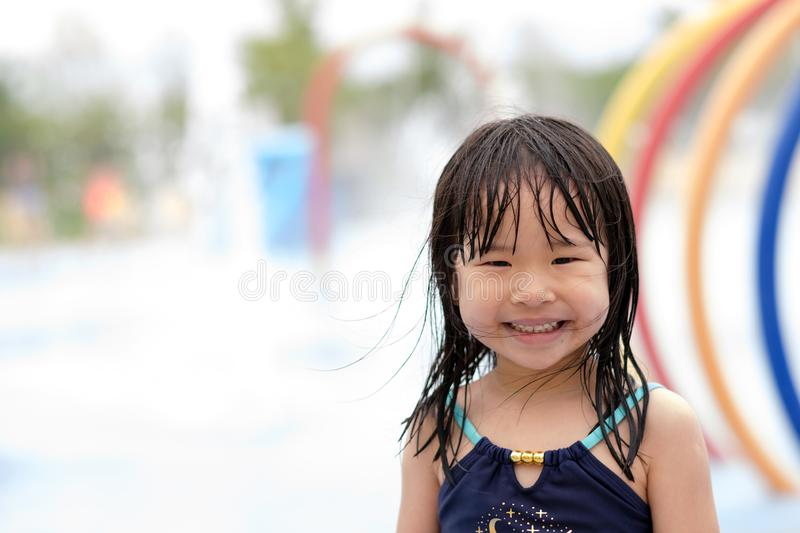Cute asian female toddler child in swimming suit. Portrait of cute asian female toddler child in swimming suit while playing with water at water park royalty free stock photo