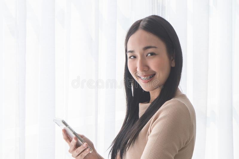 Cute Asian girl using mobile phone by morning windows stock photo