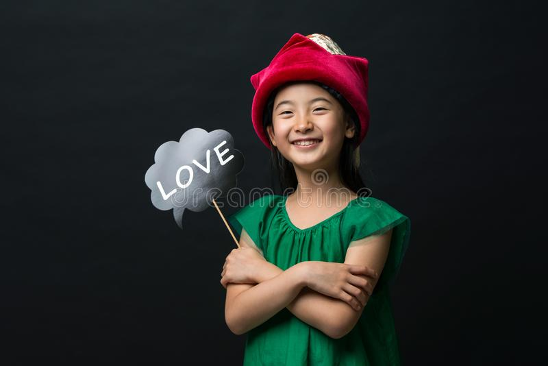 cute asian girl child dressed in a green dress holding a Christmas hat and a love stick on a black background stock photography