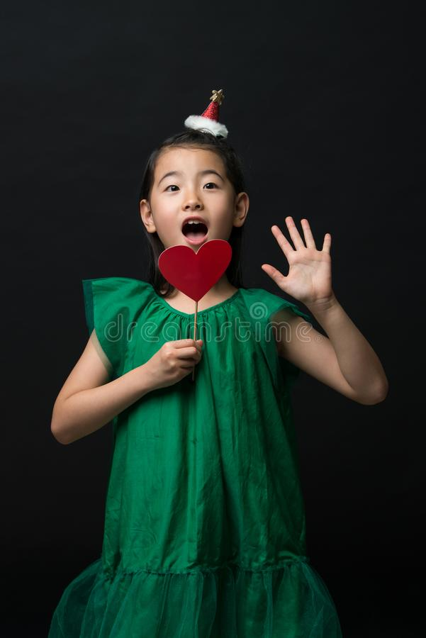 Cute asian girl child dressed in a green dress holding a Christmas ornament and a heart stick on a black background. A surprised face royalty free stock photos