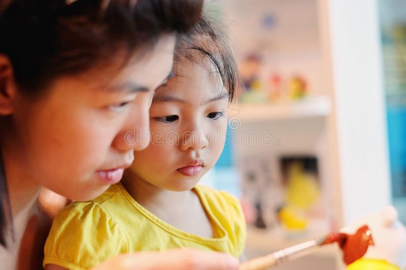 A girl doing art and craft activity with her mother, painting a plaster bear stock photos