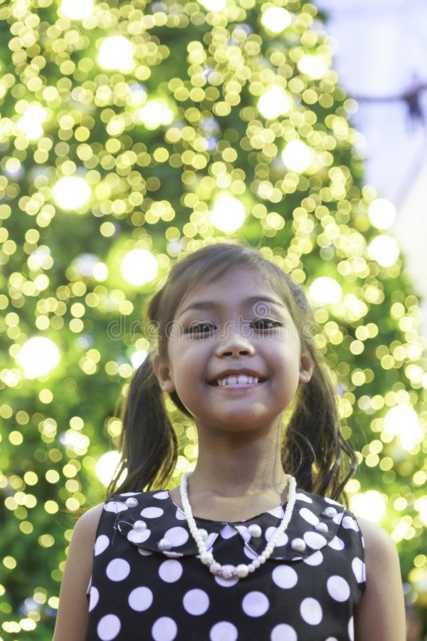 A cute asian girl enjoys with Christmas lights. A cute asian girl in black dress with white spot and tie hair enjoys with Christmas lights royalty free stock images