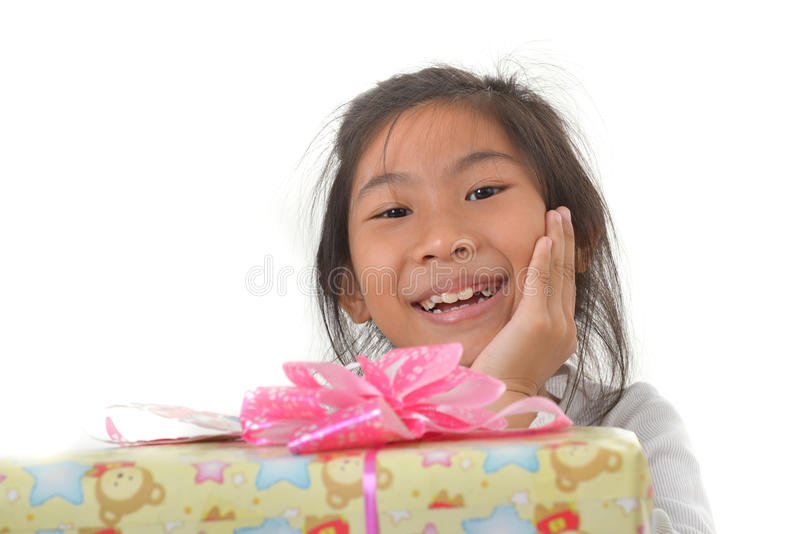 Cute Asian girl with gift on a white background. Cute Asian girl with gift on table and white background royalty free stock images