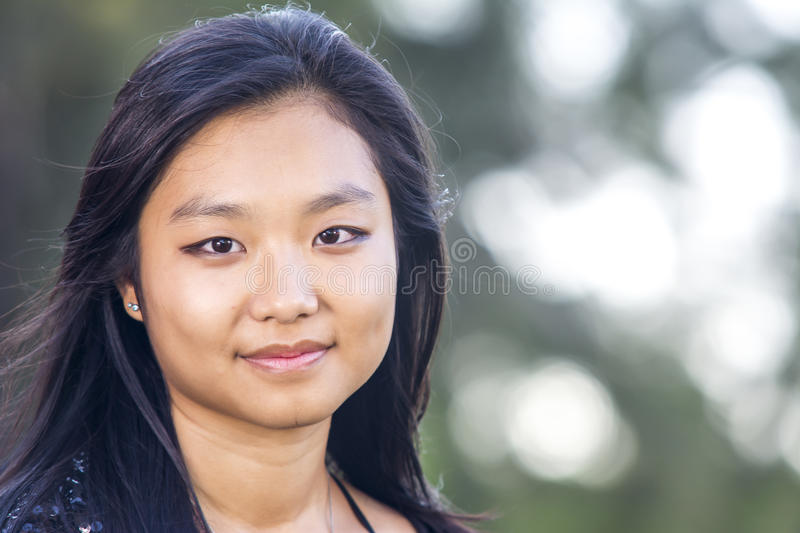 Cute asian girl smiling on blurred woods background stock photography