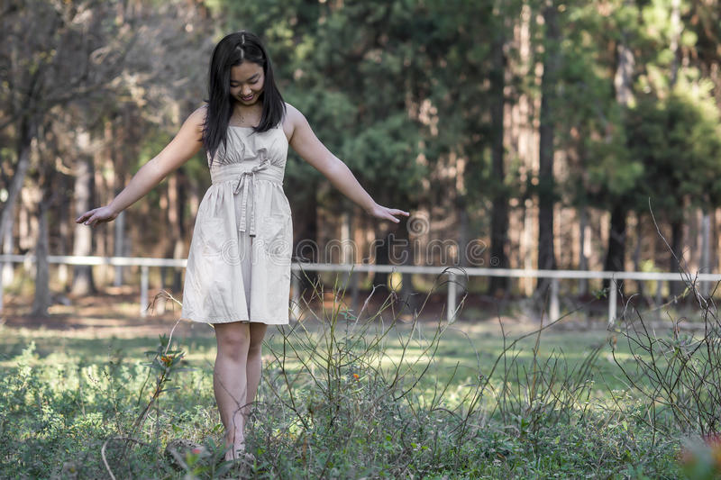 Cute funny asian girl play on the grass on blurred woods background stock image