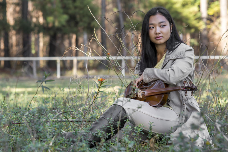 Cute asian girl on the grass with blurred woods background with a violin stock photography