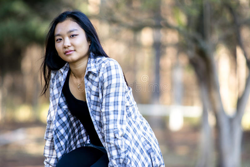 Cute asian girl smiling on blurred woods background royalty free stock image