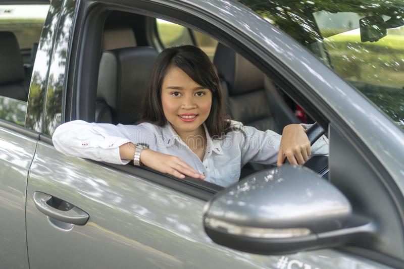 Cute Asian girl inside the car smiling and looking at the camera stock photography