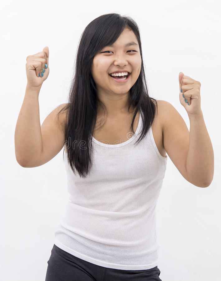 Cute happy asian girl on isolated background cheering winner royalty free stock photography