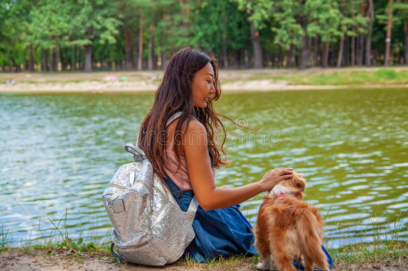 Cute asian girl with little dog walking in park. Woman sitting on green grass with dog - outdoor in nature portrait. Pet, domestic stock image