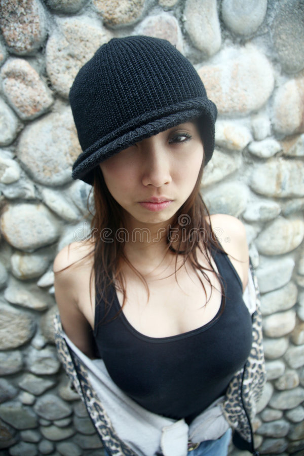 Cute Asian girl looking at viewer. Cute Asian girl with a hat looking at viewer stock photography