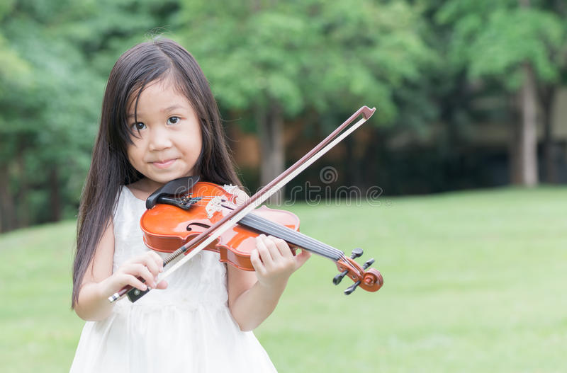Cute asian girl play violin royalty free stock photography