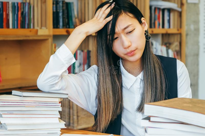 Cute Asian girl sitting in a library, surrounded by books, thinking about studying. Teen student prepares for exams, takes notes royalty free stock photos