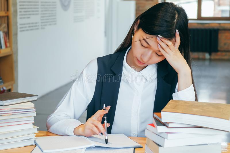 Cute Asian girl sitting in a library, surrounded by books, thinking about studying. Teen student prepares for exams, takes notes stock photography