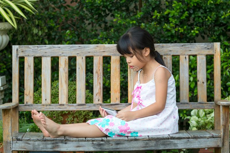 Cute Asian Girl sitting on wooden chair in park and watching cartoon in mobile phone. Which using internet for on-line channel royalty free stock photo