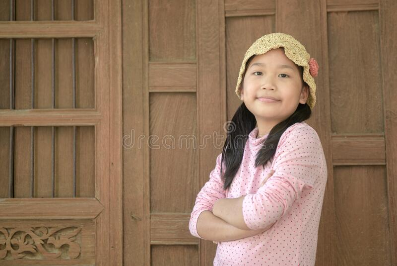 Cute asian girl smile on old wood background stock photo