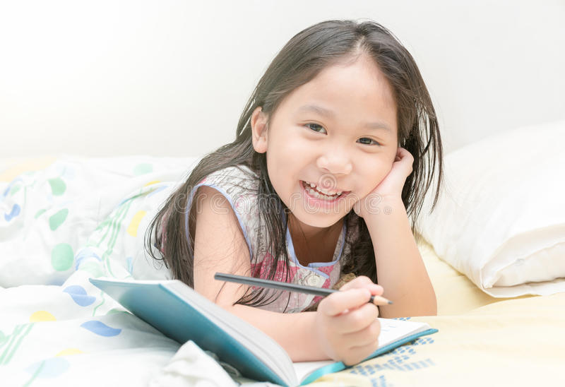 Cute asian girl smile and writing to diary on the bed royalty free stock photos