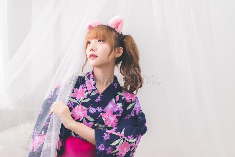 Cute Asian girl Thai people wearing yukata dress, lifted her face and grabbed the nets. In the white bedroom in the daytime. royalty free stock images