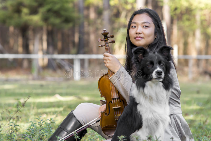 Cute asian girl with a violin withe her dog on the grass on blurred woods background royalty free stock image
