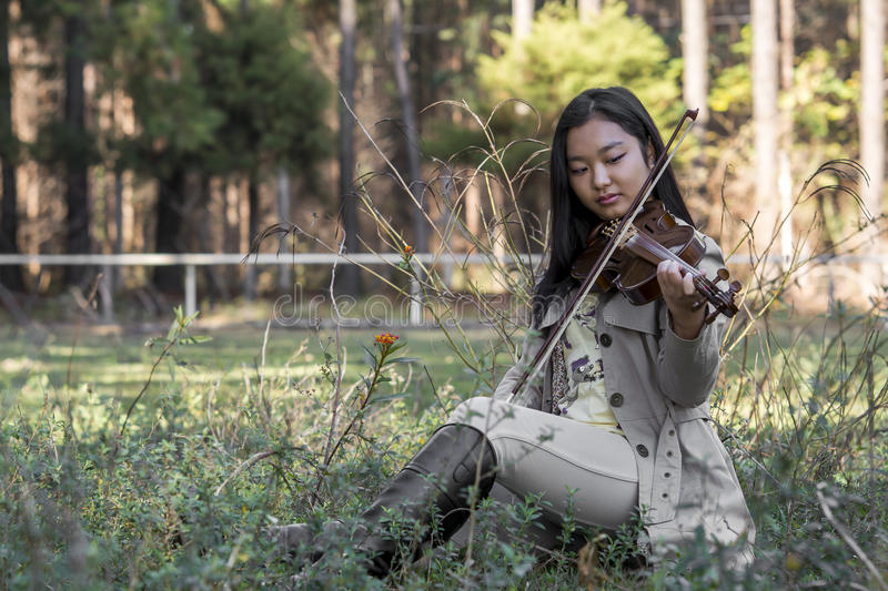 Cute asian girl with a violin on the grass on blurred woods background stock photography