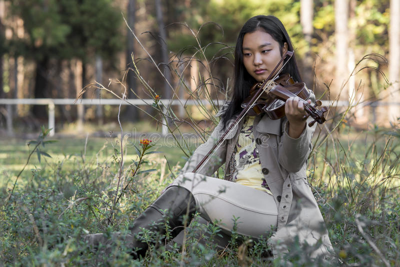 Cute asian girl with a violin on the grass on blurred woods background stock images