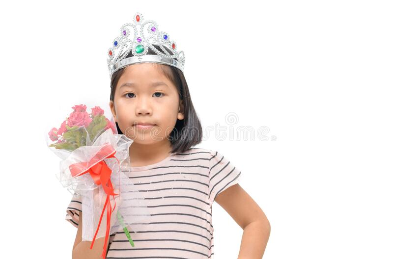 Cute Asian girl wearing diamond crown and holding a bouquet of roses stock photo