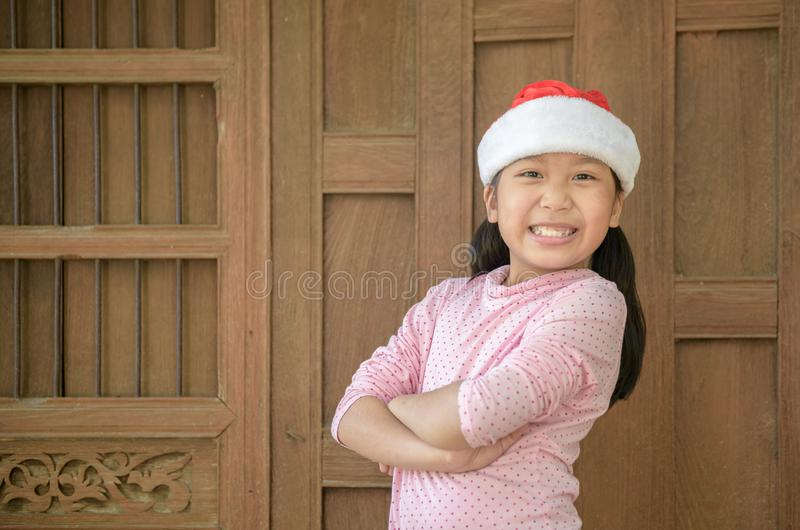 Cute asian girl wearing santa hat smile on old wood wall stock images
