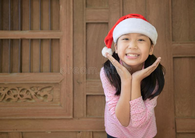 Cute asian girl wearing santa hat smile on old wood wall background stock image