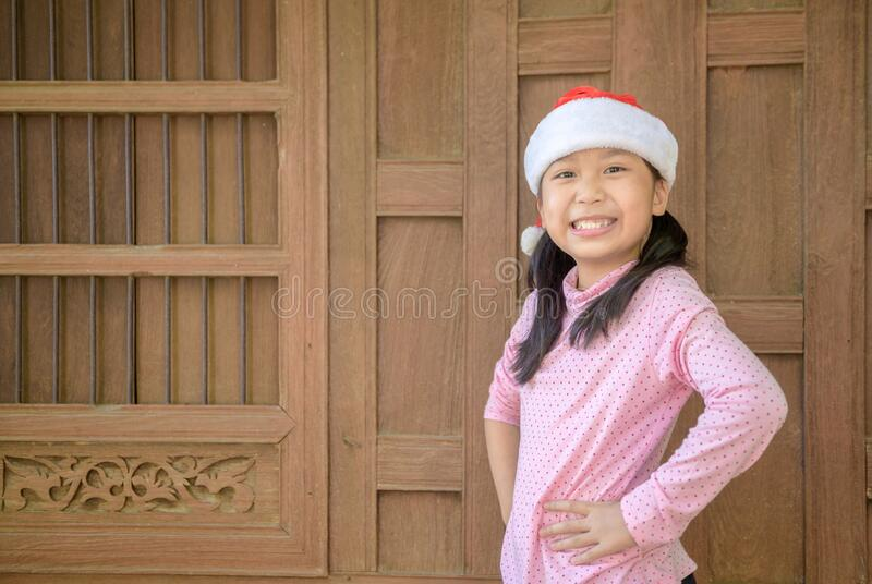 Cute asian girl wearing santa hat smile on old wood wall stock image