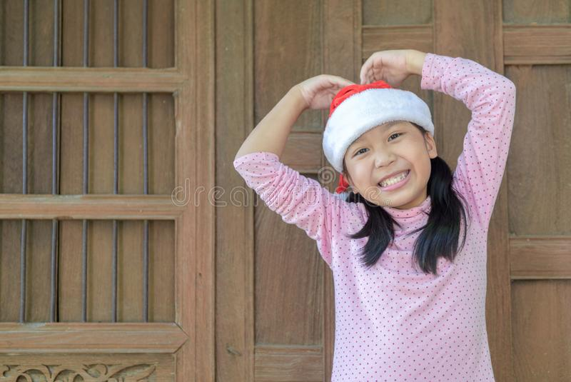Cute asian girl wearing santa hat smile on old wood wall stock photo