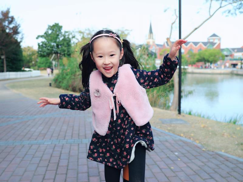 Cute Asian little beautiful girl play at autumn in the city park stock photography