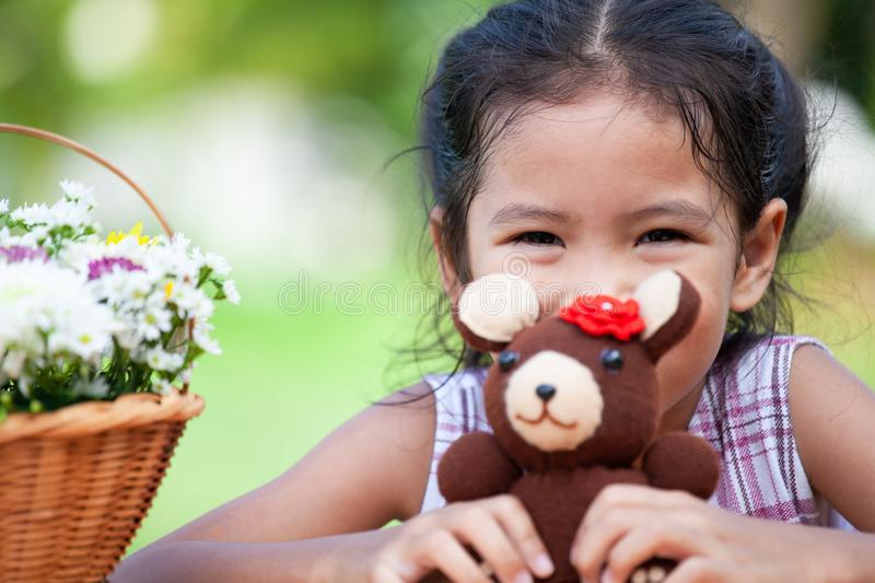 Cute asian little child girl holding her little bear doll stock photos