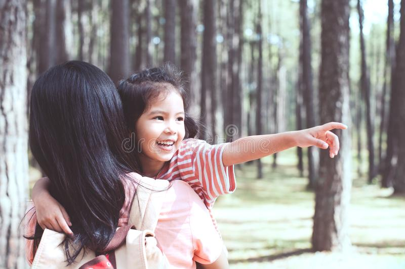 Cute asian little child girl hugging her mother with love. And pointing something in the pine tree park in vintage color tone stock photos