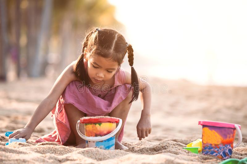 Cute asian little child girl play with sand on beach. Cute asian little child girl having fun to play with sand on beach in summer vacation stock photo